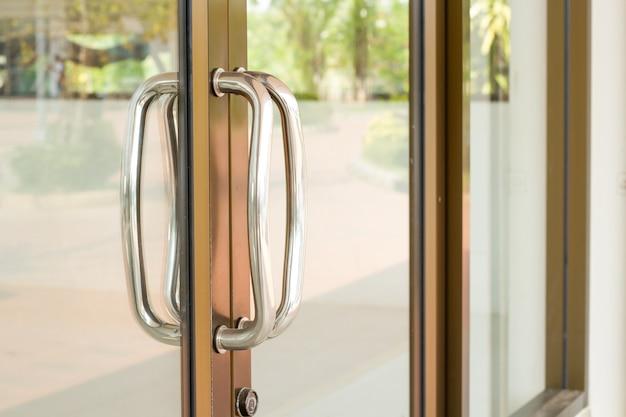 Primer plano de la manija de la puerta de vidrio de aluminio.