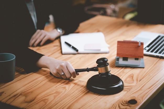 Primer plano de la mano del abogado empresaria en el anillo sosteniendo un modelo de mazo de trabajo inmobiliario en la oficina