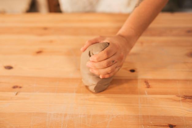 Primer plano de la mano del alfarero femenino amasando la arcilla en superficie de madera