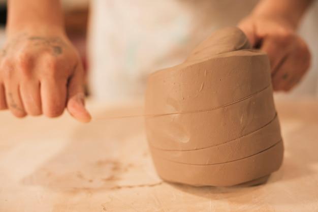 Primer plano de la mano del alfarero femenino cortando la arcilla con hilo en la mesa