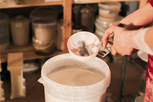 Primer plano de la mano del alfarero femenino insertando el tazón en un cubo de pintura con pinzas