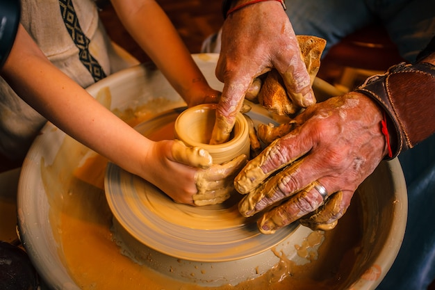 Un primer plano de la mano de un alfarero que enseña a su alumno.
