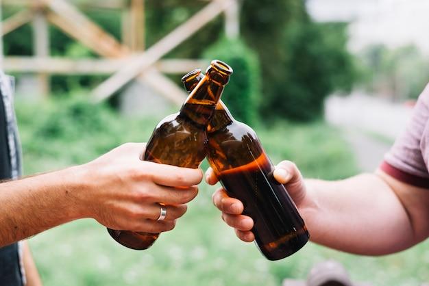 Primer plano de la mano de un amigo brindando botellas de cerveza marrón al aire libre