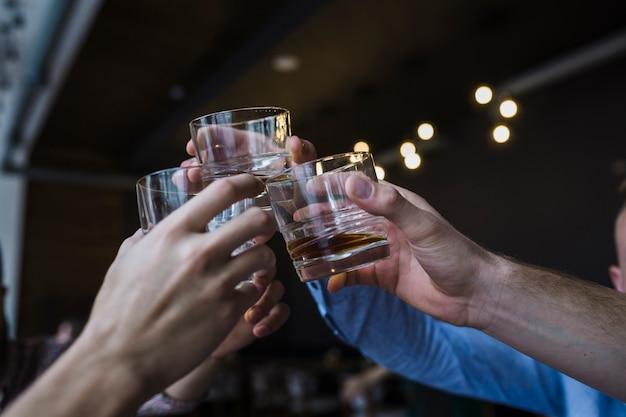 Primer plano de la mano de amigos levantando brindis con vaso de whisky