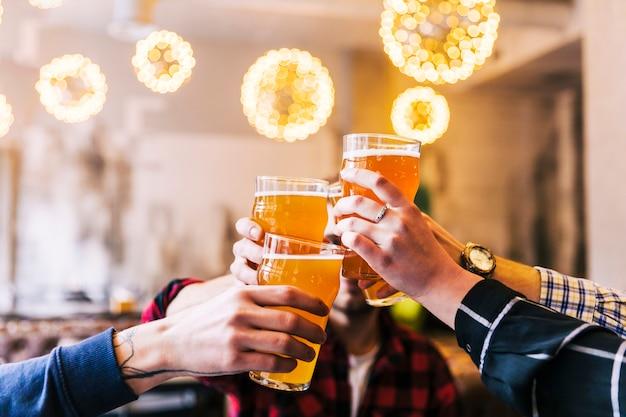 Primer plano de la mano de amigos tostado de los vasos de cerveza en la fiesta