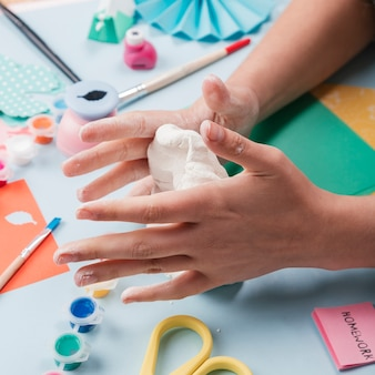 Primer plano de la mano de la artesana amasando arcilla blanca.