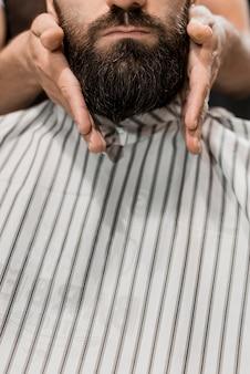 Primer plano de la mano de un barbero que prepara la barba del hombre