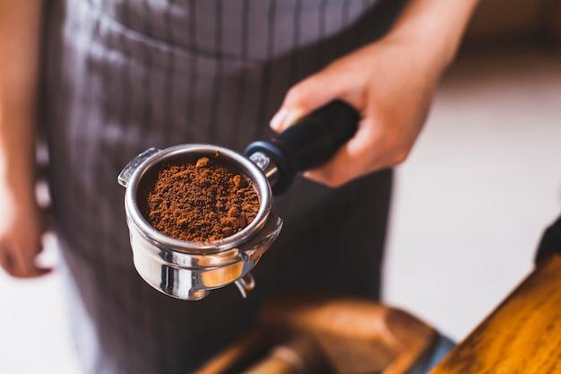 Primer plano de la mano del barista femenino que sostiene la cucharada del café express con el polvo del café