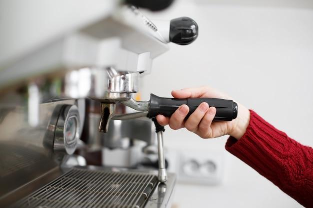 Primer plano de una mano de barista instala una taza de café para cafetera