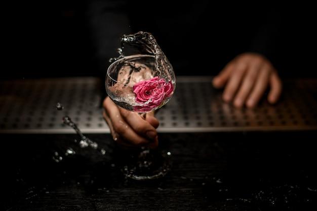 Primer plano de la mano del barman con cóctel con flor