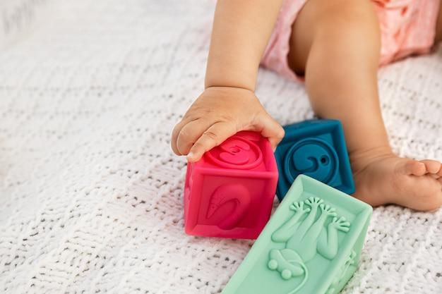 Primer plano de la mano del bebé agarrando el bloque de goma en un enfoque selectivo, el bebé sentado en una manta blanca y jugando al aire libre