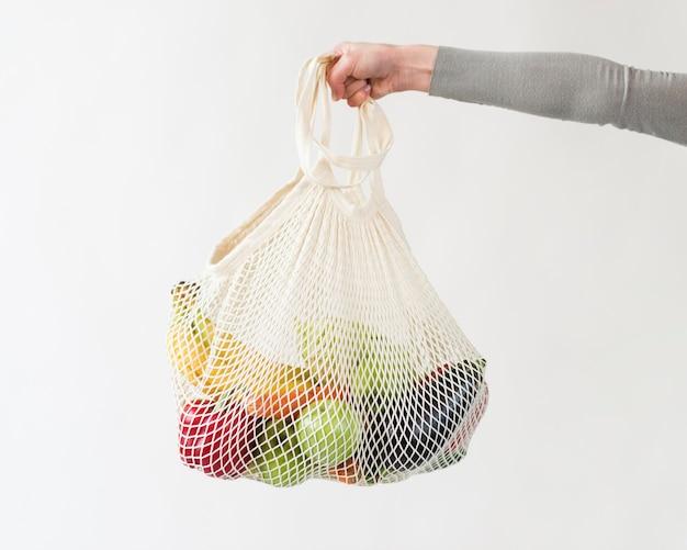 Primer plano mano bolsa reutilizable con verduras y frutas.