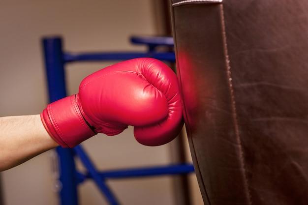Primer plano de la mano del boxeador en el momento del impacto en el saco de boxeo