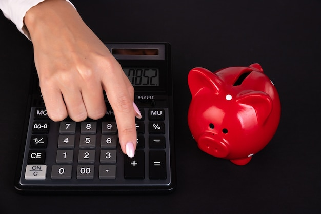 Primer plano de una mano con una calculadora y una alcancía concepto de acumulación y ahorro