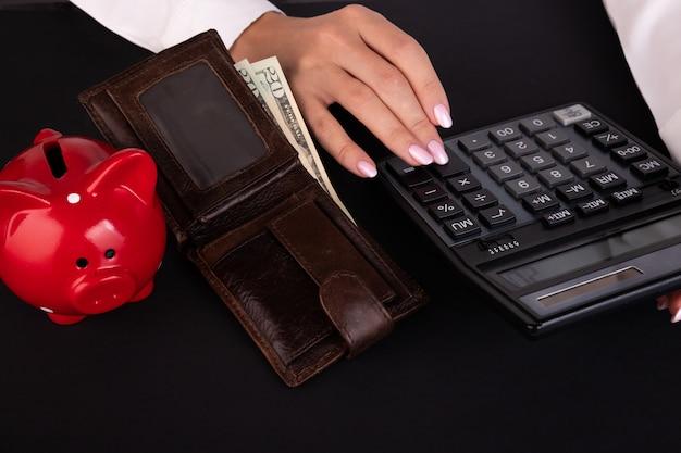 Primer plano de la mano con la calculadora billetera y ahorros hucha