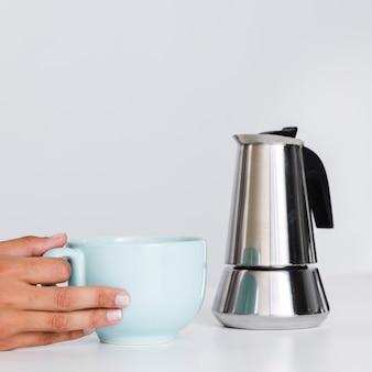 Primer plano mano caldera y taza