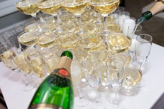 Primer plano de la mano del camarero vertiendo champán en copas