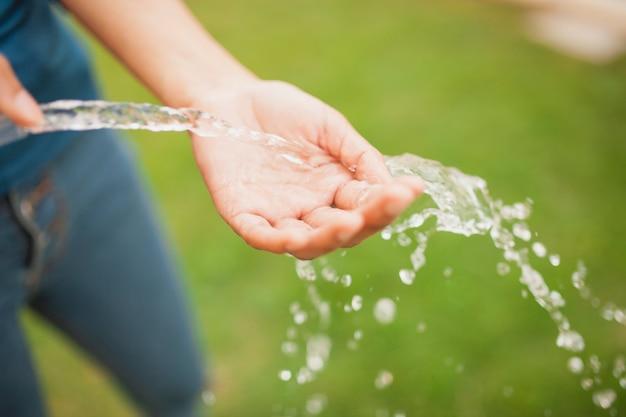 Primer plano de mano con un chorro de agua