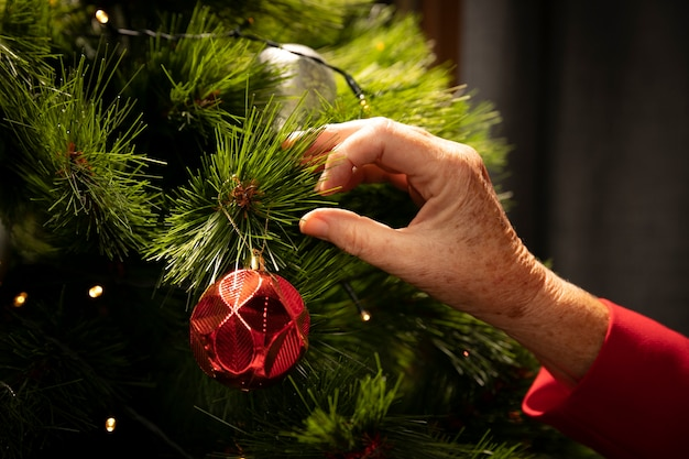 Primer plano de la mano configurando el árbol de navidad