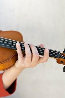Primer plano de la mano en cuerdas de violín