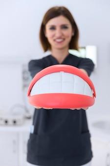 Primer plano de la mano de un dentista femenino que sostiene el modelo de los dientes