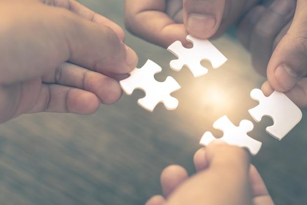 Primer plano de la mano de diversas personas que conectan el rompecabezas que es un trabajo en equipo de la empresa