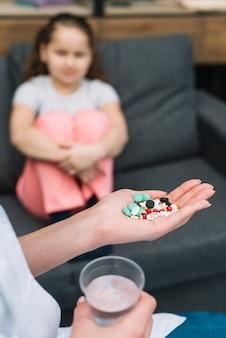 Primer plano de la mano del doctor femenino con diferentes píldoras frente a una niña sentada en el sofá