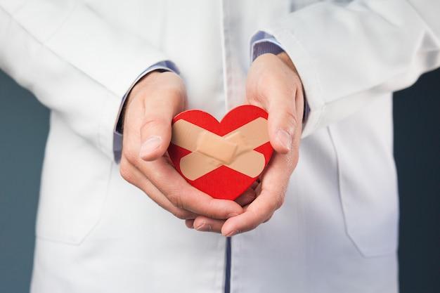 Primer plano de la mano del doctor sosteniendo corazón rojo con vendas cruzadas