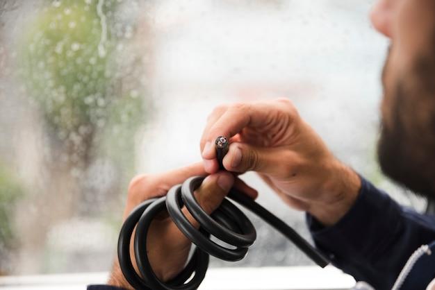 Primer plano de la mano del electricista sosteniendo cable eléctrico negro