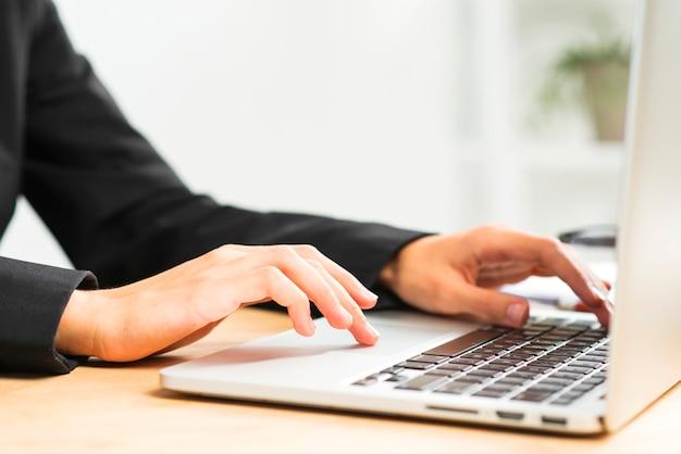Primer plano de la mano de la empresaria escribiendo en la computadora portátil sobre el escritorio