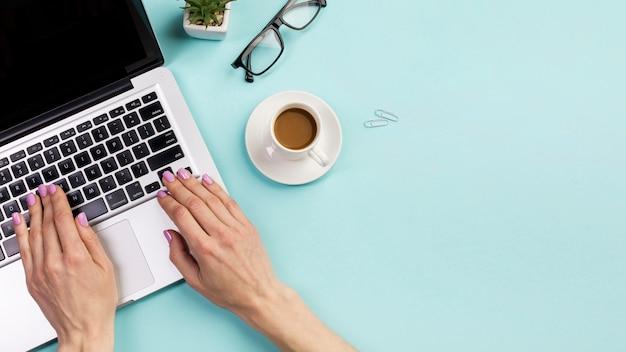 Primer plano de la mano de la empresaria escribiendo en la computadora portátil con una taza de café, lentes y