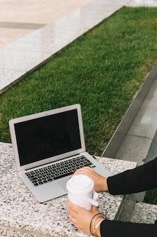 Primer plano de la mano de una empresaria usando una computadora portátil y sosteniendo una taza de eliminación