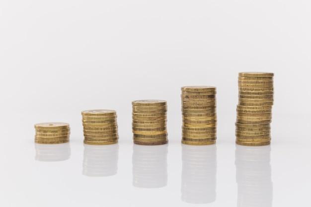 Primer plano de la mano del empresario poner monedas a la pila de monedas.