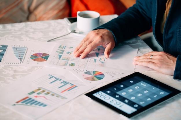 Primer plano de la mano de un empresario que analiza la factura en tableta digital sobre el escritorio,