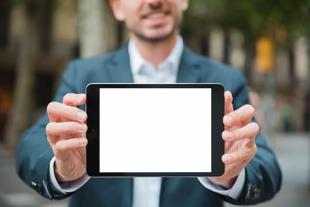 Primer plano de la mano del empresario que muestra una tableta digital con pantalla blanca
