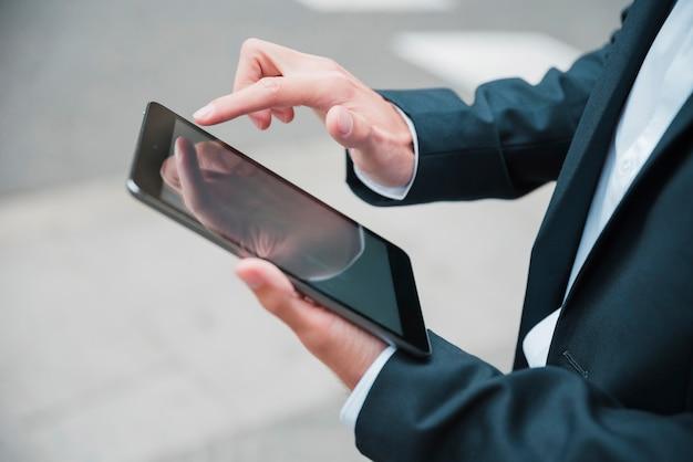 Primer plano de la mano del empresario usando tableta digital