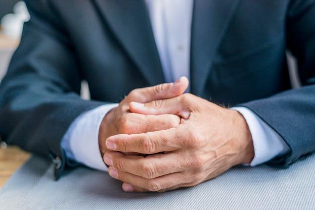 Primer plano de la mano entrelazada de un hombre de negocios