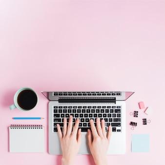 Primer plano de la mano escribiendo en la computadora portátil con artículos de papelería y una taza de café sobre fondo rosa
