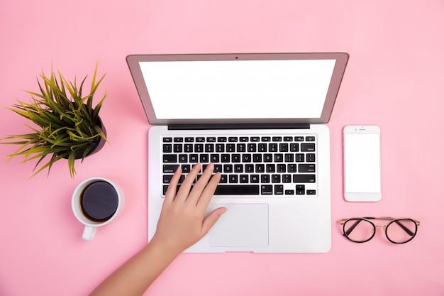 Primer plano de la mano escribiendo en la computadora portátil con papelería y una taza de café sobre fondo rosa