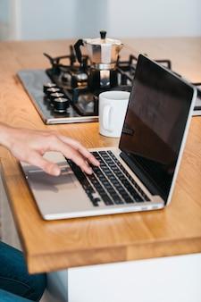 Primer plano de la mano escribiendo en la computadora portátil sobre el mostrador de la cocina de madera con taza de café