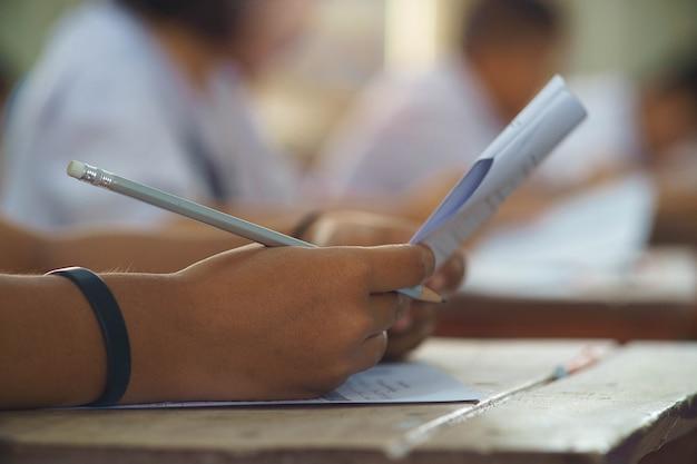 Primer plano a mano de un estudiante sosteniendo un lápiz y tomando un examen en el aula con estrés para la prueba de educación.