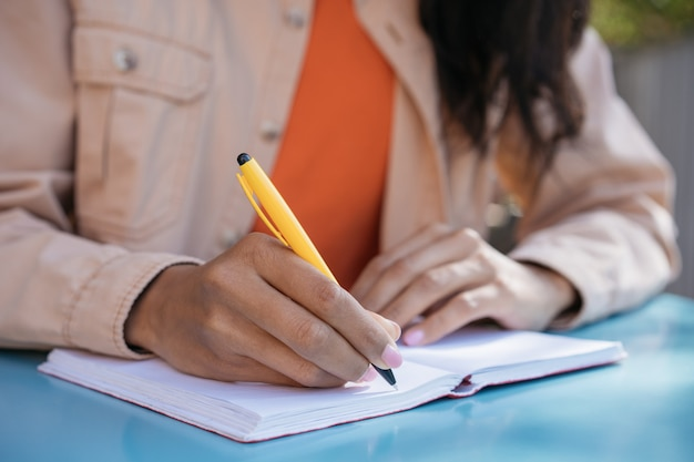 Primer plano de la mano del estudiante sosteniendo la pluma, escribiendo en el cuaderno, estudiando, aprendiendo el idioma, preparación de exámenes, concepto de educación