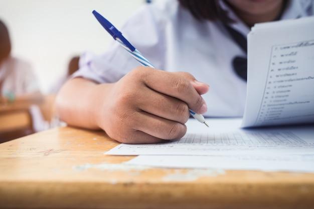 Primer plano de la mano de los estudiantes que escriben un examen en el aula con estrés