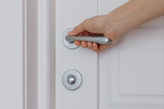 Primer plano de mano femenina se abre, cierra la puerta interior blanca