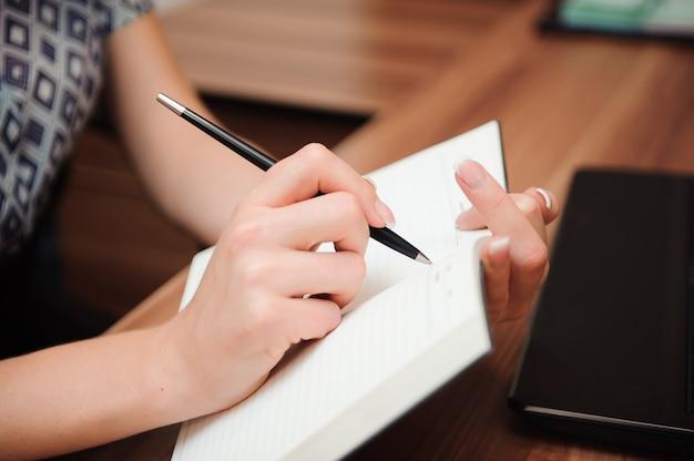 Primer plano de una mano femenina escribiendo en un cuaderno en blanco con un bolígrafo