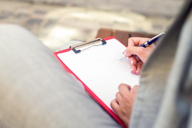Primer plano de una mano femenina escribiendo en un planificador en blanco con una pluma.