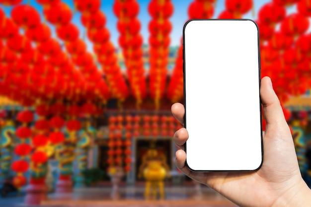 Primer plano de la mano femenina que sostiene el smartphone en la hermosa decoración de farolillos rojos chinos para el festival del año nuevo chino en el santuario chino
