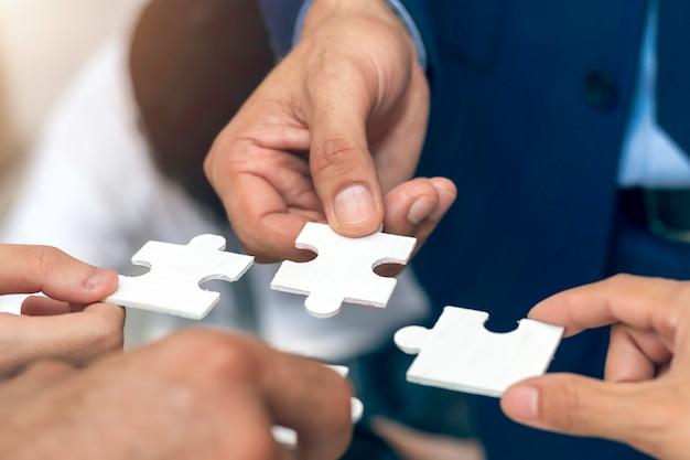 Primer plano, mano de gente de negocios con rompecabezas.