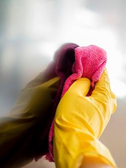 Primer plano de mano con guante de goma desinfectante