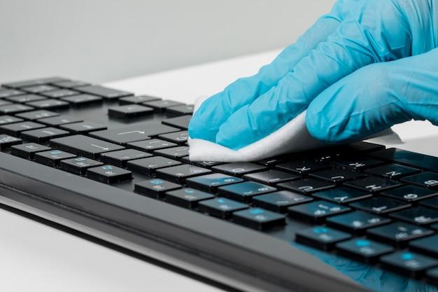 Primer plano de la mano con guante quirúrgico desinfectando el teclado